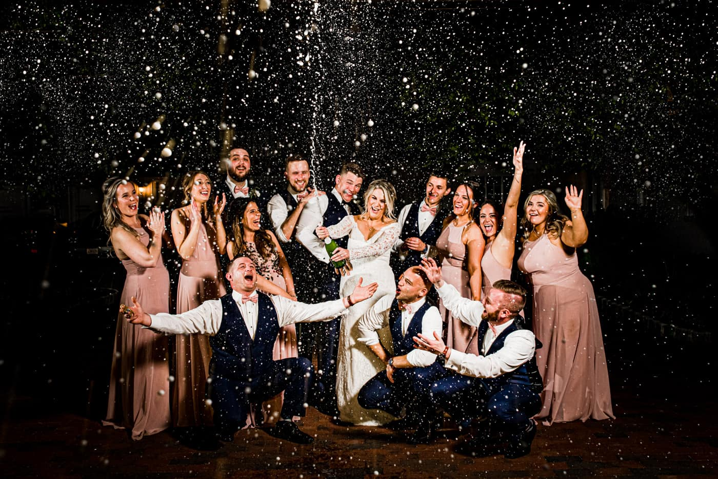 bridal party spraying champagne