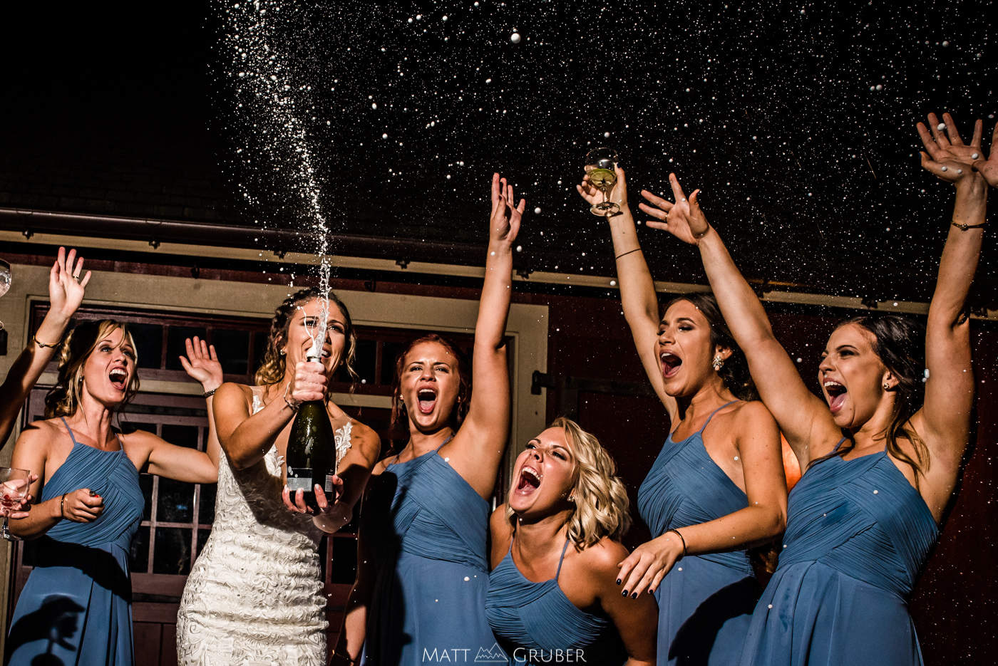 Bridesmaids popping champagne