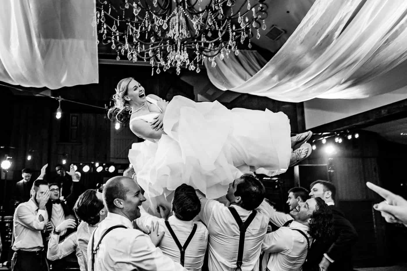 Bride getting tossed in the air