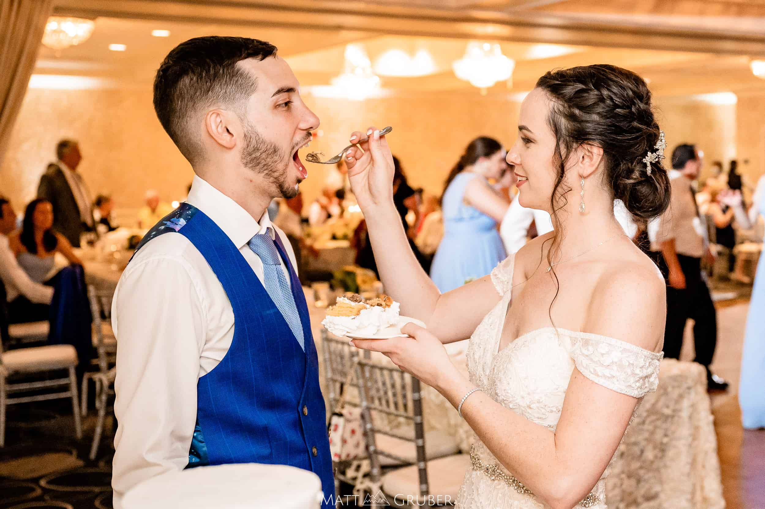 bride and groom feeding each other wedding cake at Springfield country club