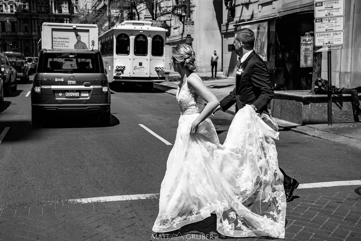 bride and groom walking across Broad Street in Philadelphia