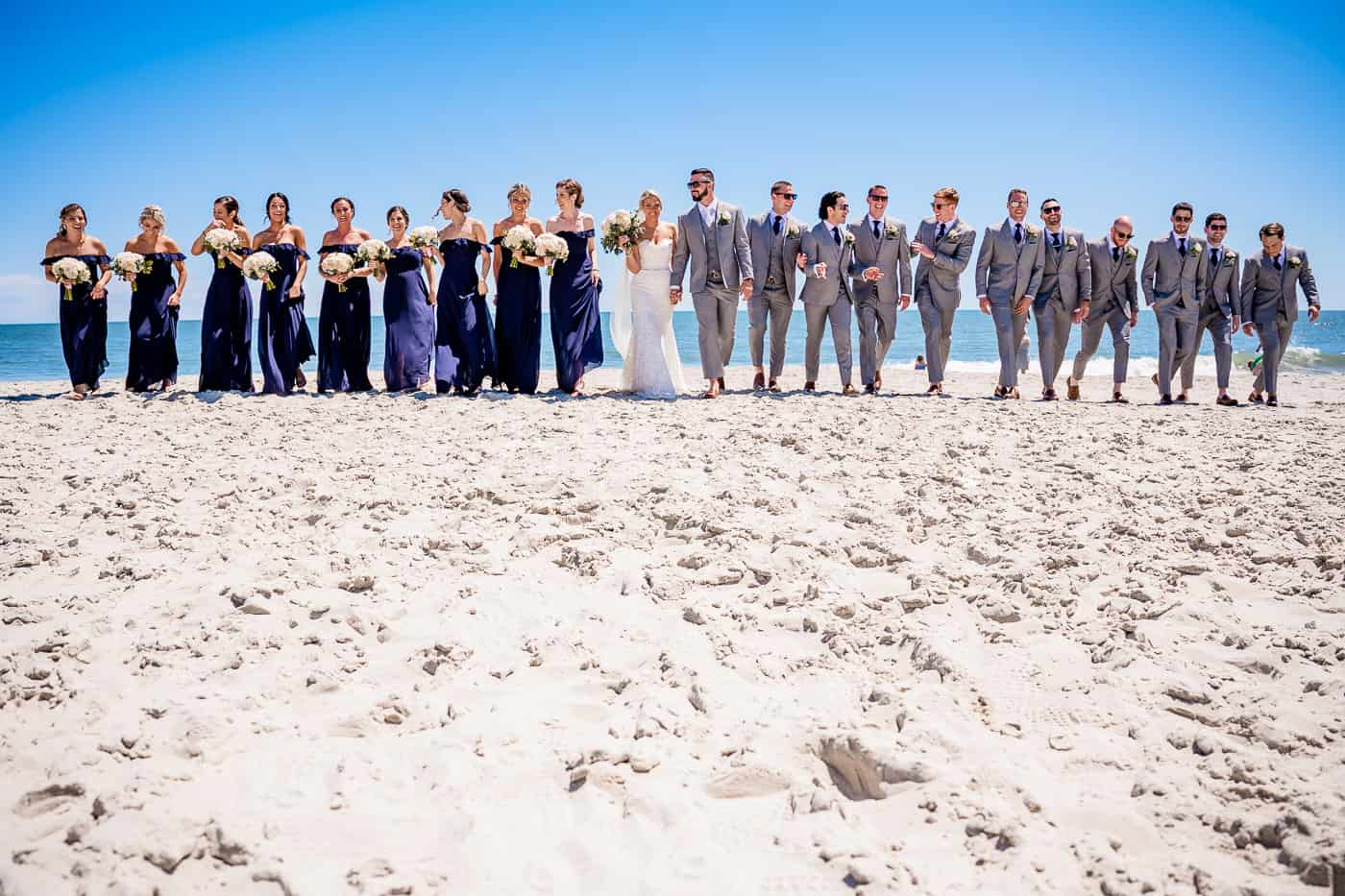 bridal party walking along the beach at a wedding at icons diamond beach in wildwood New Jersey