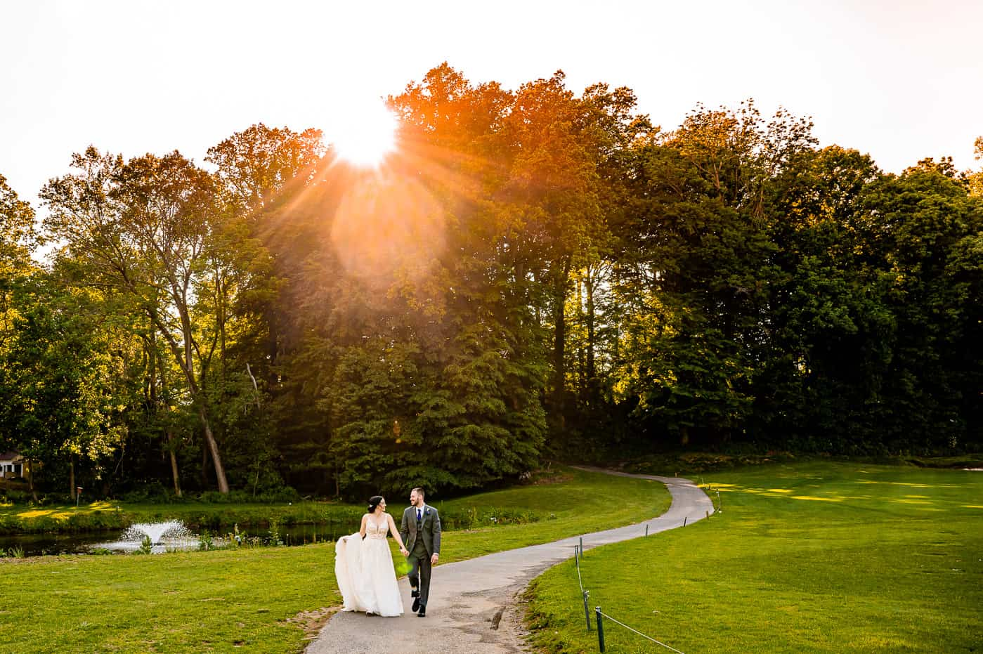 Bride and groom walking through Paxon hollow golf club at sunset