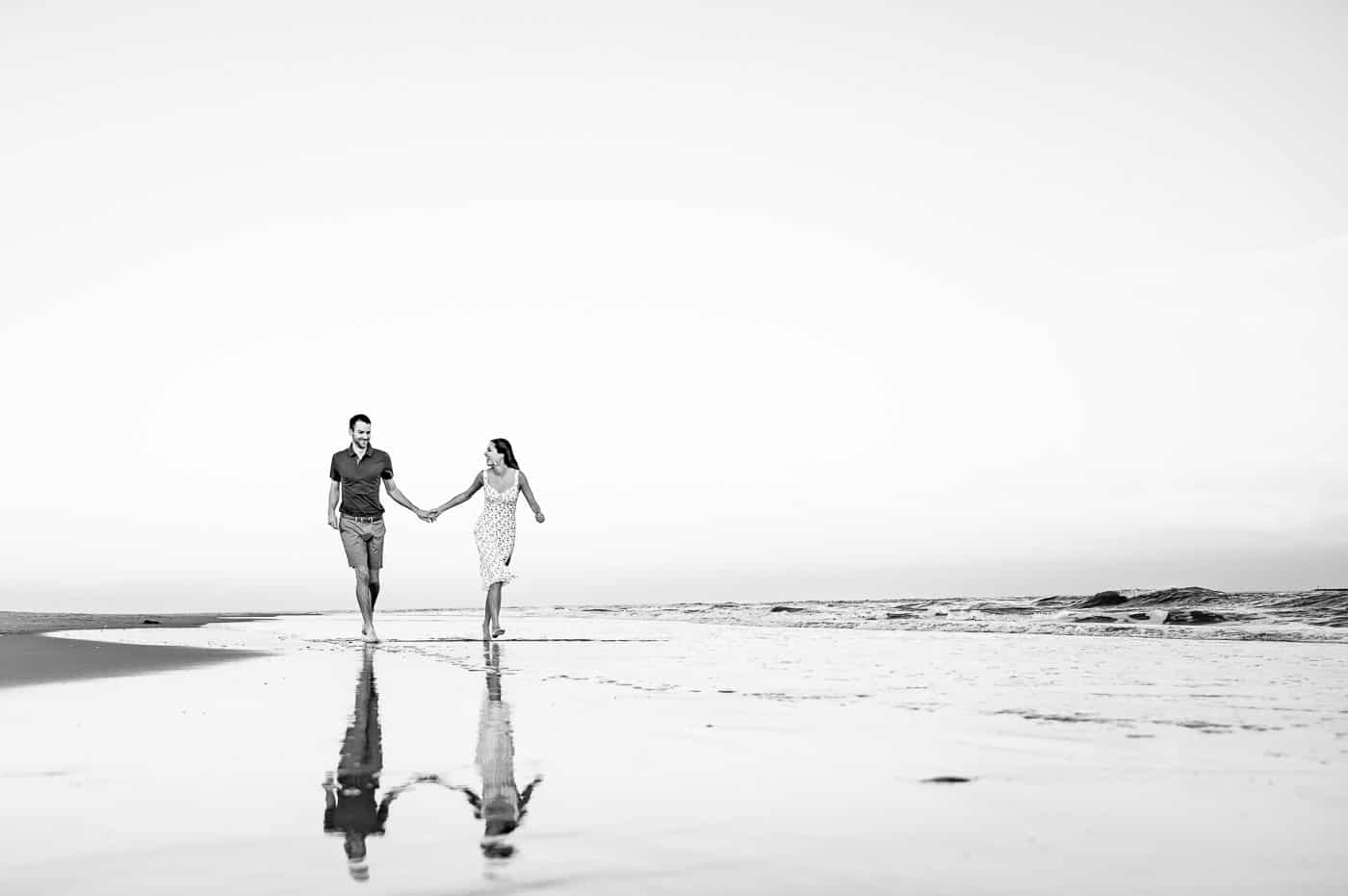 bride and groom running through the water in sea isle city