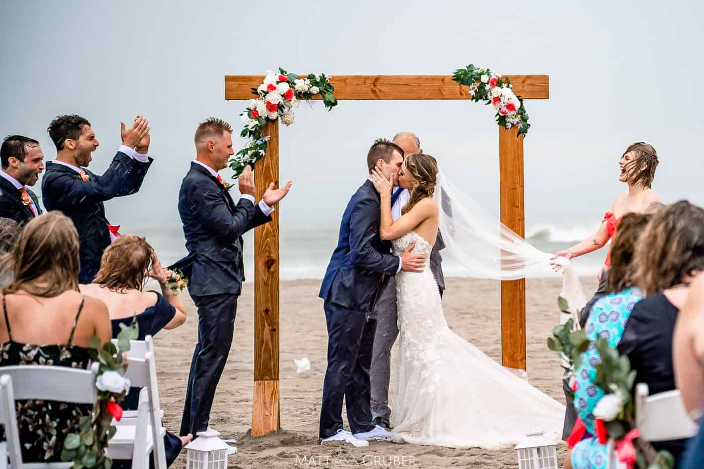 romantic first kiss in the rain during wedding ceremony on the beach at ICONA Avalon