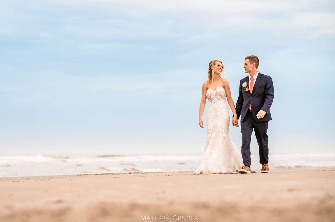 bride and groom walk along the beach during golden hour at ICONA Avalon