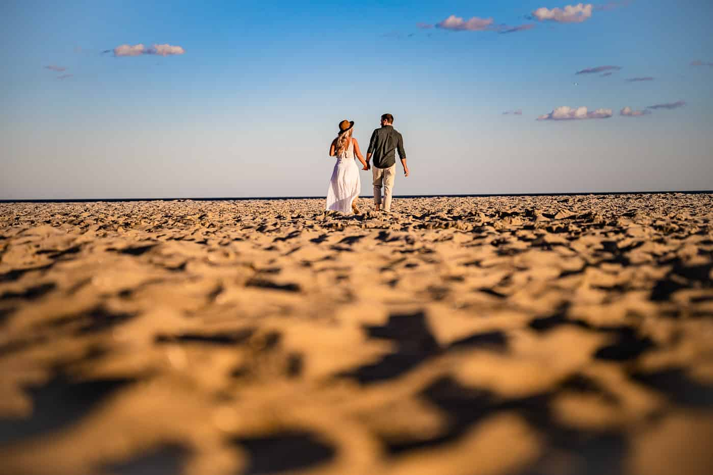 bride and groom walk along the san in cape may during their engagement session