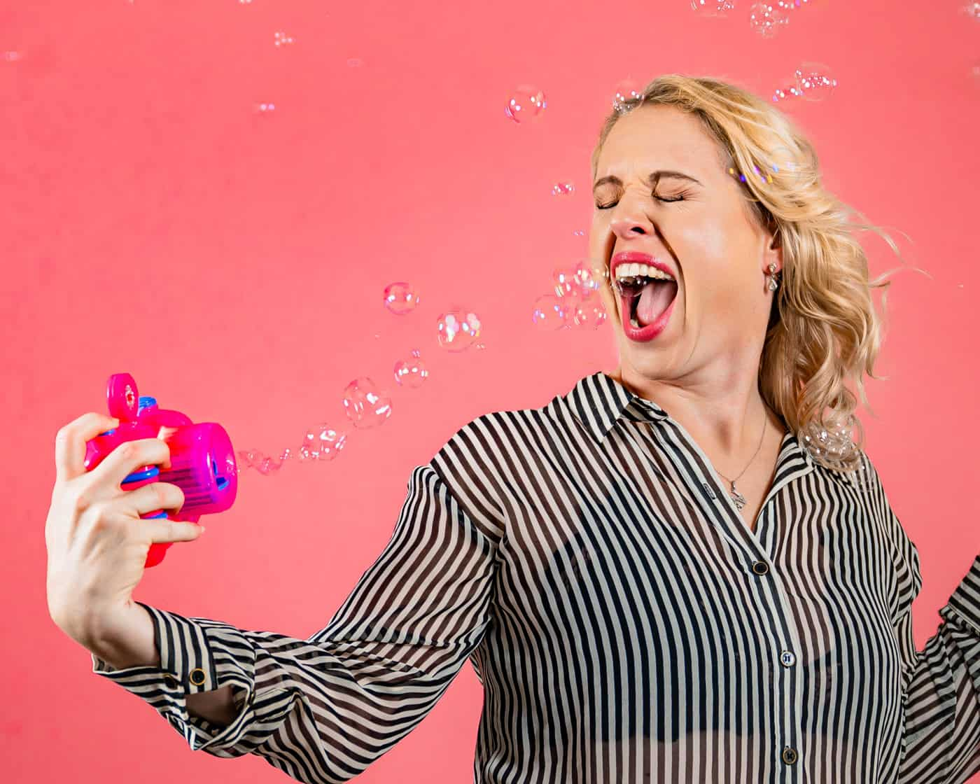 woman shoots bubble machine in her mouth
