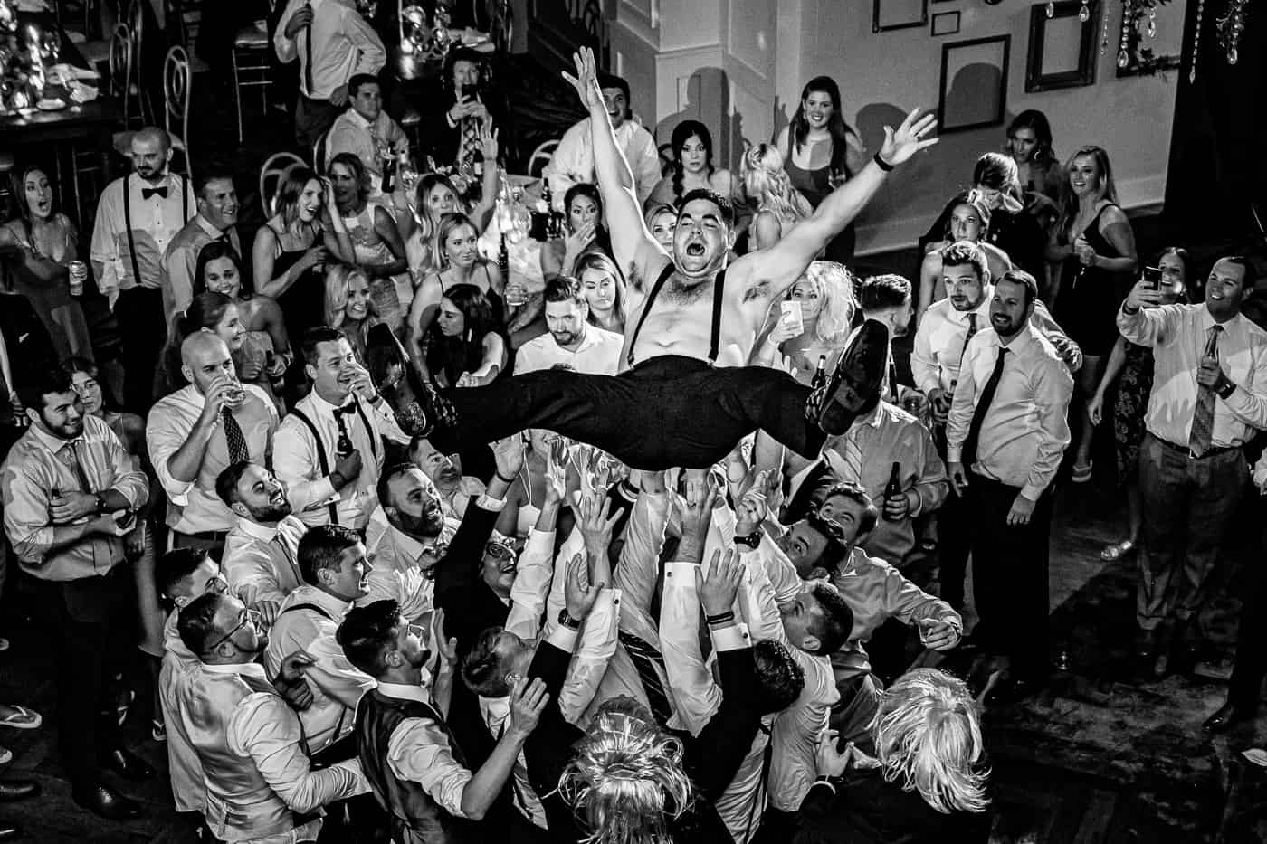 groom being tossed into the air at wedding reception at the Lucy by cescaphe